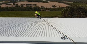 roofer on the roof with safety harness